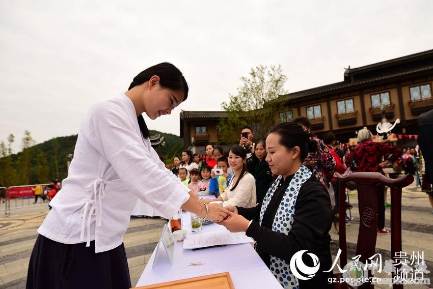 10月4日,在贵州省黔东南苗族侗族自治州丹寨县万达小镇,茶艺师在茶艺比赛中向评委奉茶。杨武魁 摄